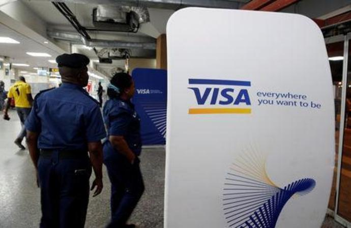 FILE PHOTO:  Security staff stand next to a Visa logo at Murtala Muhammed International Airport before the arrival of the Nigerian Women