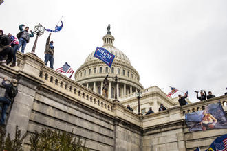 A pro-Trump mob climbs the Capitol building in Washington, Jan.