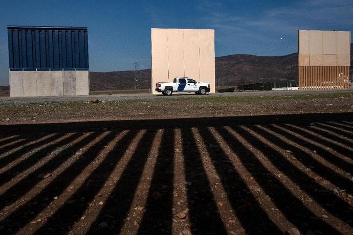 A US Customs and Border protection vehicle passes by prototypes for US President Donald Trump