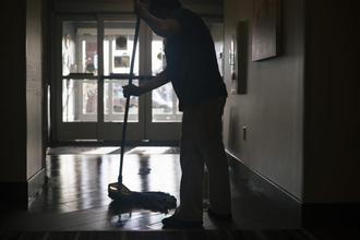 A worker cleans the front entry area inside a Hampton Inn & Suites near Dulles International Airport in Herndon, Va.