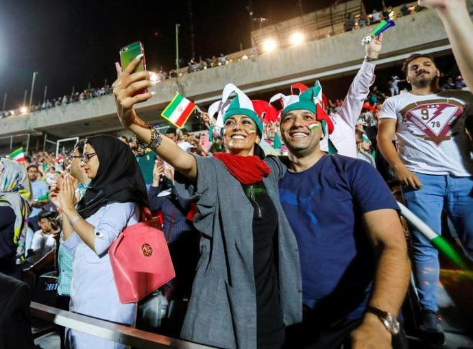 "An Iranian couple pose for a ""selfie"" while cheering for their national fooball team during a screening of a Russia 2018 World Cup Group B football match between Iran and Spain at Azadi stadium in Tehran on June 20, 2018"