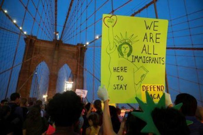 People march across the Brooklyn Bridge to protest the planned dissolution of DACA in Manhattan, New York City, U.