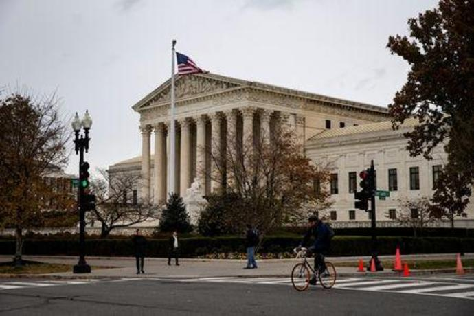FILE PHOTO: A man rides a bicycle past the Supreme Court in Washington