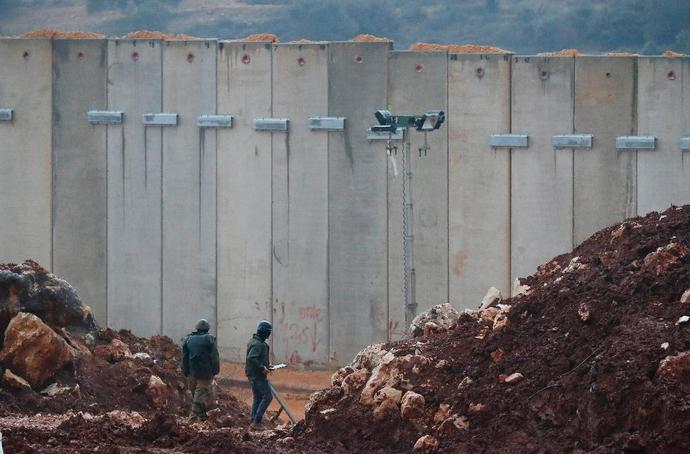 Israeli soldiers stand near the concrete barrier erected along the border with Lebanon near the northern Israeli town of Metula on December 19, 2018
