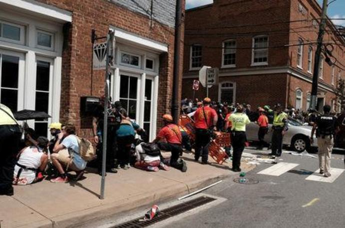 "FILE PHOTO: Rescue workers assist people who were injured when a car drove through a group of counter protesters at the ""Unite the Right"" rally in Charlottesville"