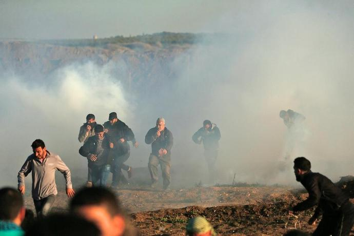 Palestinian protesters run through tear gas fumes during clashes with Israeli forces during a demonstration along the border with Israel east of Gaza City on January 11, 2019