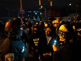 Protesters speak to police officers during a protest in Rochester, N.