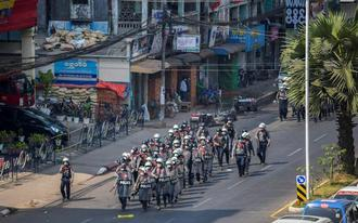 Riot police officers advance on pro-democracy protesters during a rally against the military coup in Yangon - REUTERS