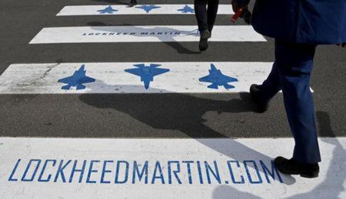FILE PHOTO - Trade visitors are seen walking over a road crossing covered with Lockheed Martin branding at Farnborough International Airshow in Farnborough, Britain