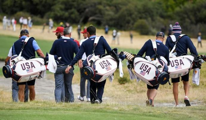 US team caddies follow their players during a practice round ahead of the Presidents Cup this week