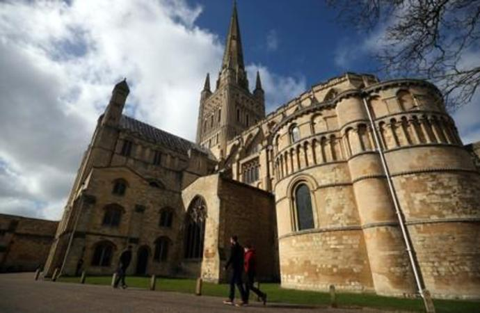 FILE PHOTO: People walk past Norwich Cathedral in Norwich