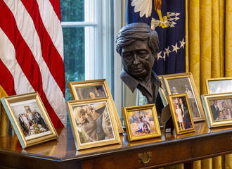 A sculpted bust of Cesar Chavez oversees a collection of personal framed photos on a table in the Oval Office awaiting President Joseph Biden at the White House in Washington, DC.