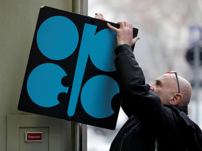 FILE PHOTO: A man fixes a sign with OPEC