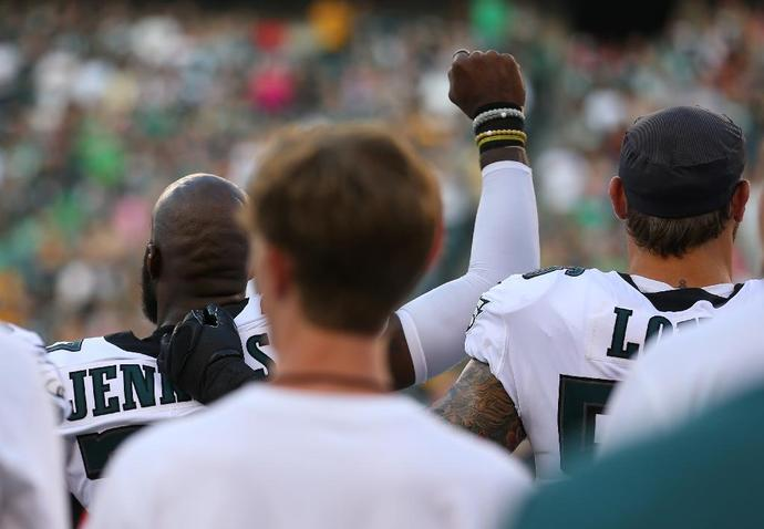 Malcolm Jenkins #27 of the Philadelphia Eagles raises his fist during the national anthem as Chris Long #56 puts his arm around him prior to the preseason game against the Pittsburgh Steelers