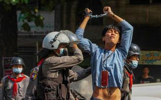 A pro-democracy protester is detained by riot police officers during a rally against the military coup in Yangon - REUTERS