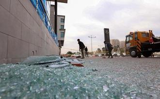 Image: A worker cleans shattered glass outside a damaged shop following a rocket attack the previous night in Irbil, the capital of the northern Iraqi Kurdish autonomous region (Safin Hamed / AFP - Getty Images file)
