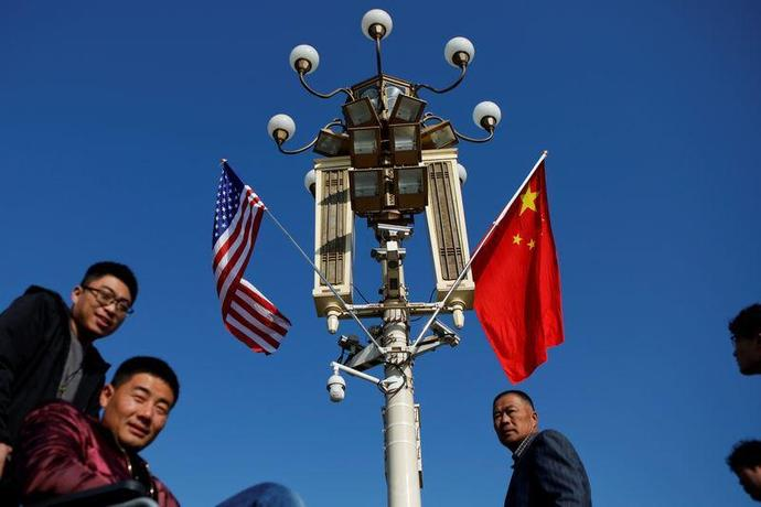 People pass a pole with security cameras, U.S. and China