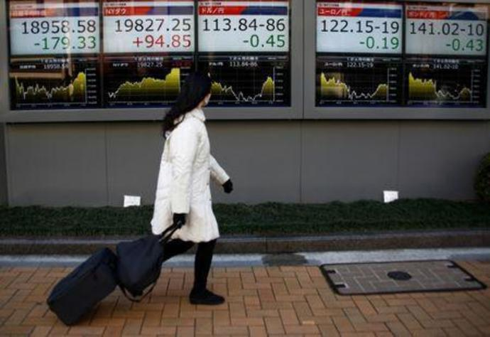 A woman walks past electronic board showing stock prices and Japanese Yen