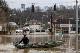 Justin Wade drives a boat down Main Street after high water and flooding filled downtown Beattyville after heavy rains led Kentucky River waters overflowing Sunday evening.
