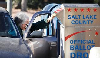 A voter drops off her mail in ballot at a dropbox at the Salt Lake County election office in Salt Lake City, Utah, on Oct.