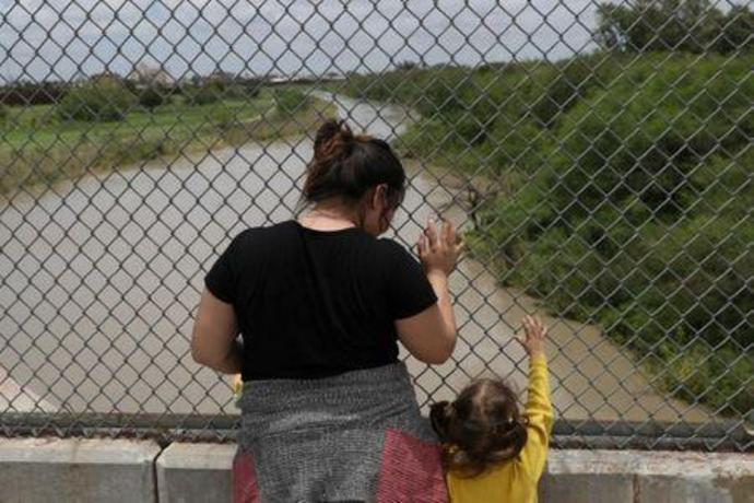 A Honduran mother and daughter seeking asylum wait on the Mexican side of the Brownsville-Matamoros International Bridge after being denied entry by U.S. Customs and Border Protection officers near Brownsville
