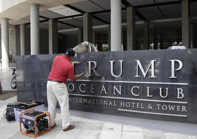 A man removes the sign from the former Trump Ocean Club ijn Panama City on March 5, 2018