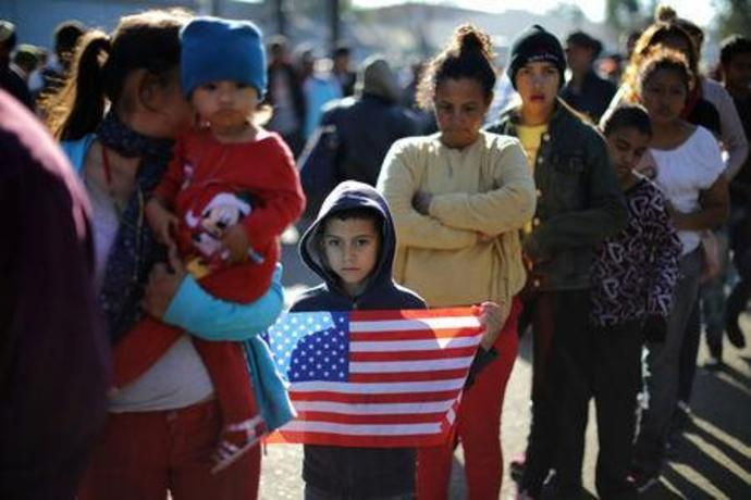 FILE PHOTO: Marie Orellana, 28, and her seven-year-old son Angel, from Honduras, part of a caravan of thousands of migrants from Central America trying to reach the United States, queue for food outside a temporary shelter in Tijuana