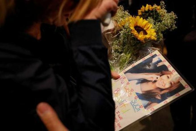 A mourner arrives with a picture of one of her friends at a vigil for the victims of the mass shooting in Thousand Oaks