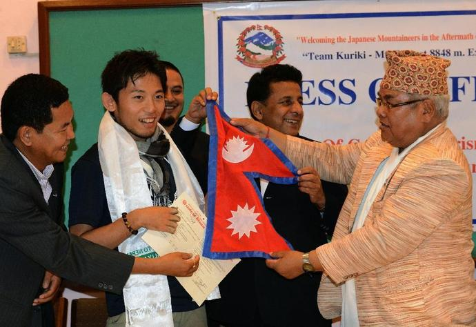 Photo taken in August  2015 shows Japanese climber Nobukazu Kuriki (2nd L) accepting a permit to climb Everest and a Nepalese flag from Nepal