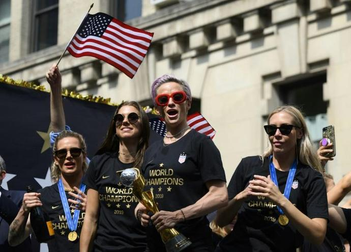 In this photo taken on July 10, 2019 Megan Rapinoe (C) and other members of the World Cup-winning US women