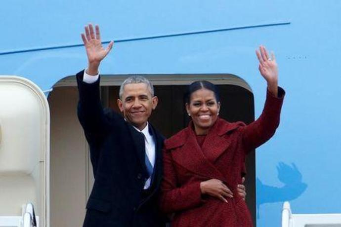 FILE PHOTO - Former president Barack Obama waves with his wife Michelle as they board a Boeing 747 at Joint Base Andrews