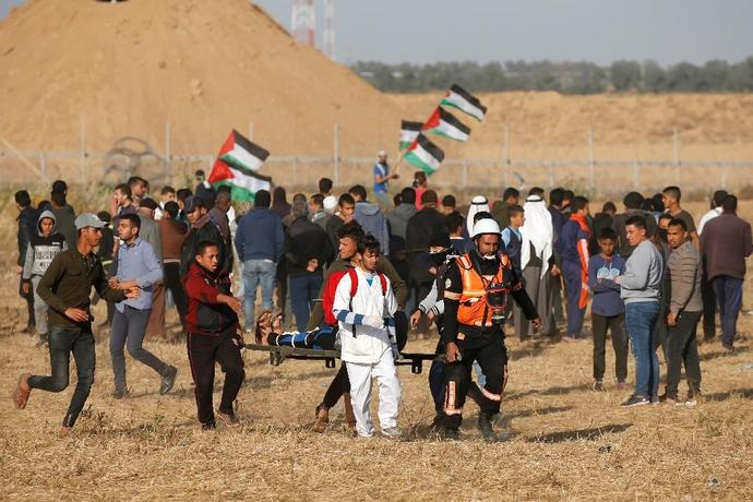 Palestinian paramedics carry a wounded protester during a demonstration near the border between Israel and the Gaza Strip on April 12, 2019