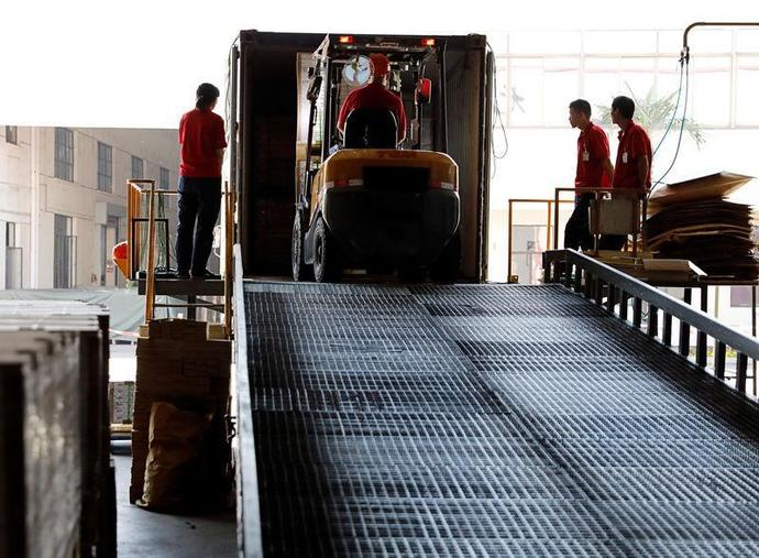 Employees transport PVC plastic flooring to a container truck in Zhangjiagang Yihua Rundong New Material Co.