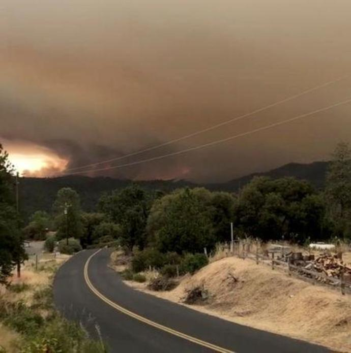 Flames and smoke rise from a treeline in Mariposa County, California
