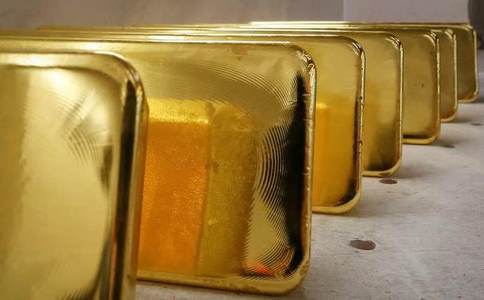 Gold inches down as hawkish Fed weighs on safe-haven demand
