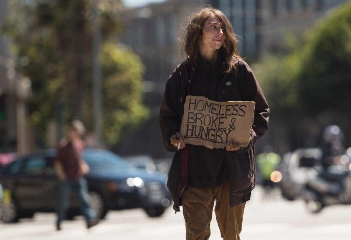 A homeless person begs on a center divider in San Francisco, California