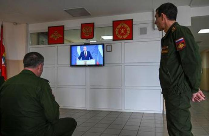 Officers of Cossack cadet corps watch a television broadcast of Russian President Vladimir Putin addressing the Federal Assembly, at a settlement of Rassvet outside Rostov-On-Don