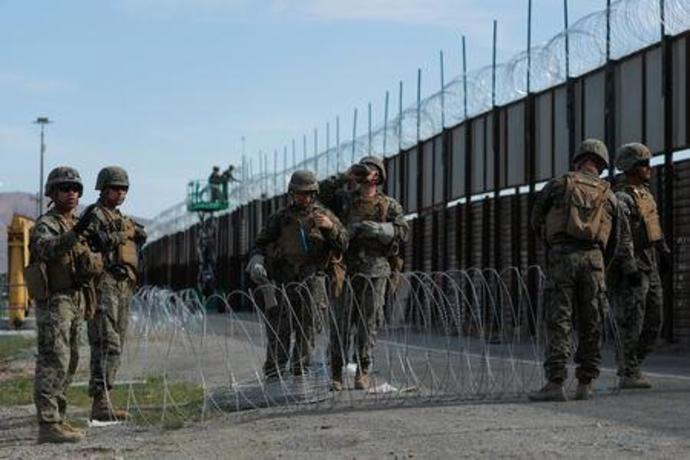 U.S. Marines deploy concertina wire along the primary wall at the U.S. Mexico border in San Diego