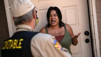 A tenant speaks with a Maricopa County constable who arrived with an eviction order in Phoenix.