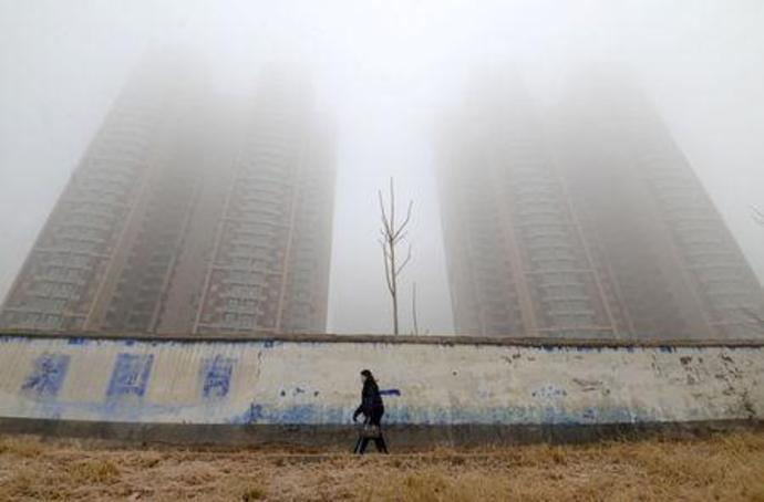 Woman wearing a mask walks past buildings on a polluted day in Hebei