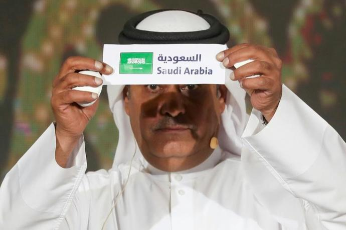A member of the Qatar Football Association holds up the name of Saudi Arabia during the group draw for the Arabian Gulf Cup in the capital Doha
