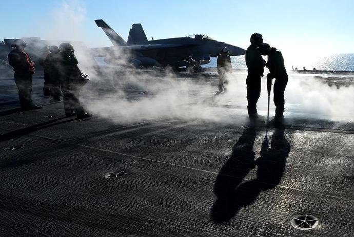 An F/A-18E Super Hornet prepares for takeoff from the flight deck of the USS Nimitz in 2013