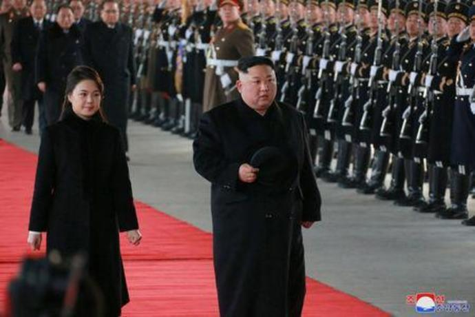 North Korean leader Kim Jong Un and wife Ri Sol Ju inspect an honour guard before leaving Pyongyang for a visit to China
