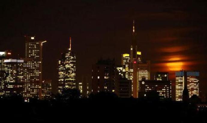 FILE PHOTO - The moon is partly covered by clouds as it rises above the skyline of Frankfurt