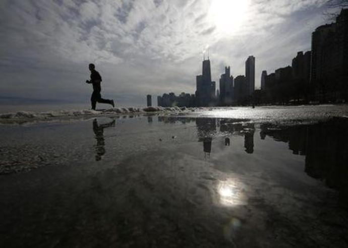 A jogger is reflected in a puddle as he runs along the beach in Chicago,