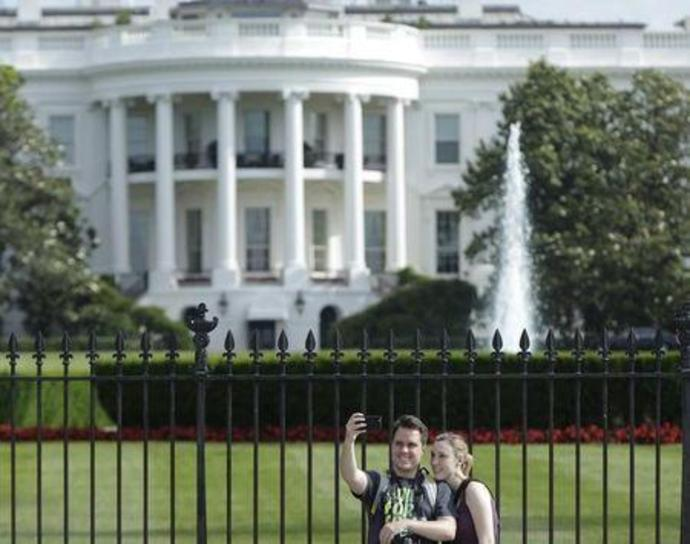 Tourists take selfies by the original South Lawn security fencing at the White House in Washington May 28, 2015.