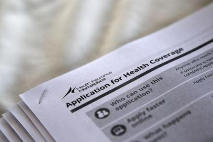 FILE PHOTO - Applications are seen at a rally held by supporters of the Affordable Care Act in Jackson, Mississippi